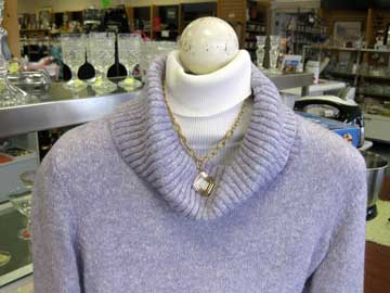 recycle your wardrobe - woman's white turtleneck under lavender-colored cowl neck sweater and necklace