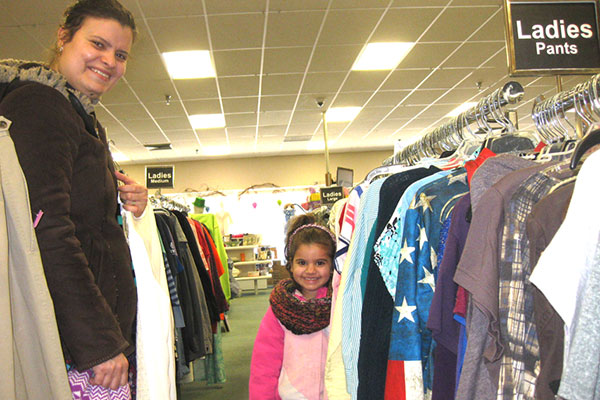 A tall smiling mom and her little girl pose for the camera in the women's clothes section of Nu2u Resale Shop in Tinley Park.