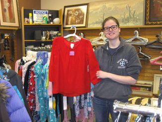 A young woman in glasses and wearing a gray hoodie holds a red child's blouse from the Nu2u Resale children's clothes rack.