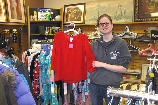 A young woman in glasses and wearing a gray hoodie holds a red child's blouse from the Nu2u kid's clothes rack.