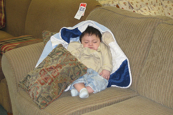 A baby in a white and blue blanket is sleeping on a couch in the Nu2u Resale Shop in downtown Tinly Park